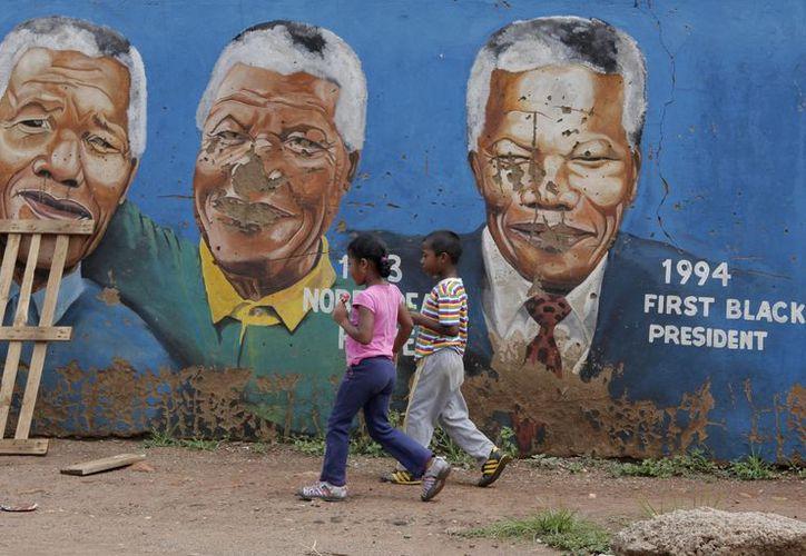 Dos niños pasan delante de una pintada con retratos de Nelson Mandela en Soweto, Johannesburgo. (EFE)