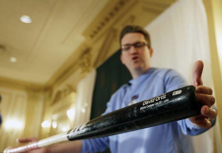 Brad Horn, empleado del Salón de la Fama del Béisbol, muestra un bate utilizado en la Serie Mundial de 2013 por el dominicano David Ortiz. (Agencias)