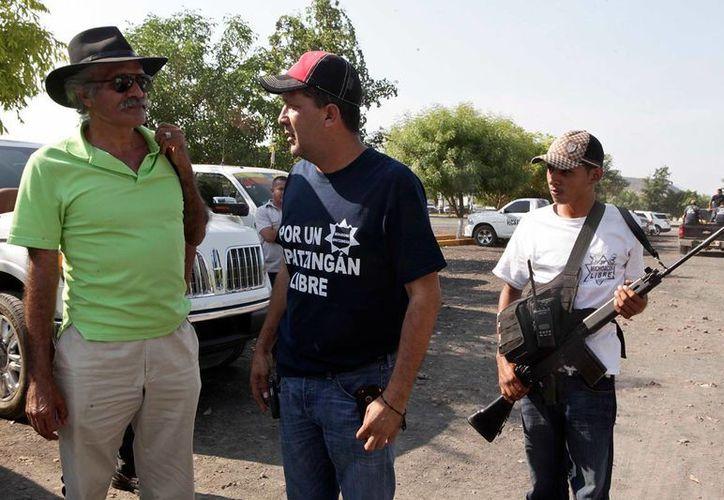 José Manuel Mireles y Alberto Gutiérrez 'Comandante 5' (c) durante una reunión de autodefensas en Michoacán. ( Germán Canseco/proceso.com.mx)