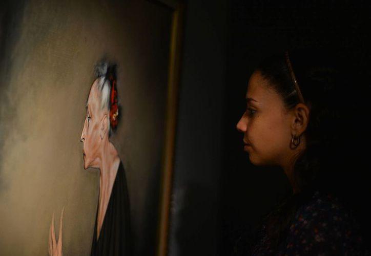Los personajes de la muestra parecen deambular sin rumbo. En la imagen una joven admira una de las pinturas de Rafael Coronel.  (Milenio Novedades)