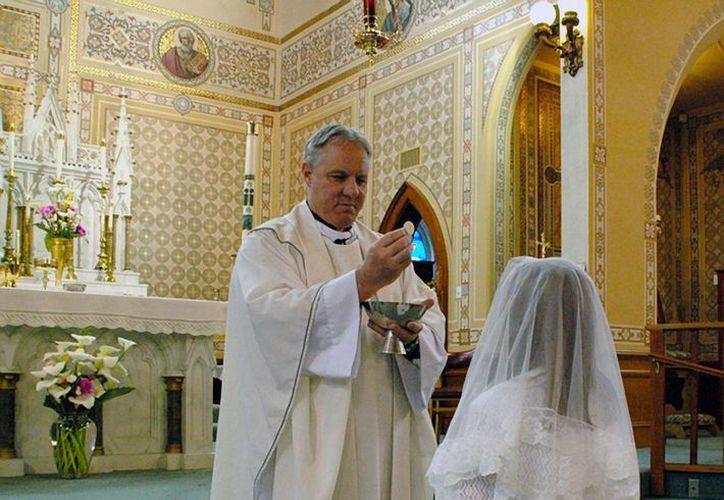 El reverendo Eric Fredd durante la entrega de la comunión en la iglesia católica de Saint Bernard, en Eureka, California. Se investiga su muerte. (Agencias)