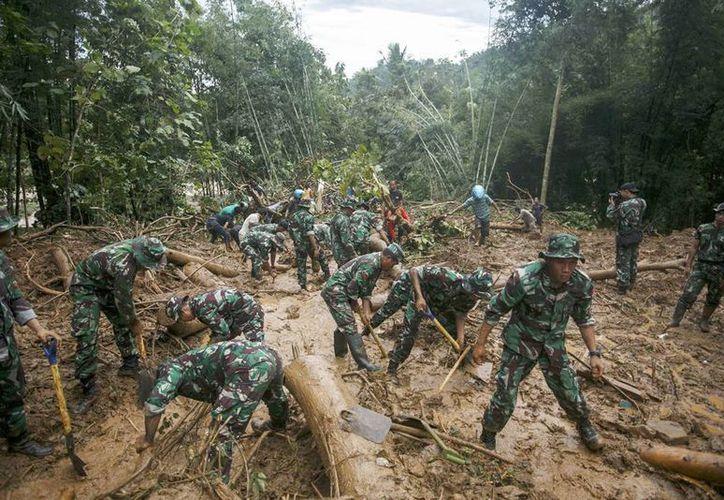 Soldados indonesios buscan víctimas en la aldea de Purworejo, Indonesia tras las inundaciones por lluvias. (EFE)