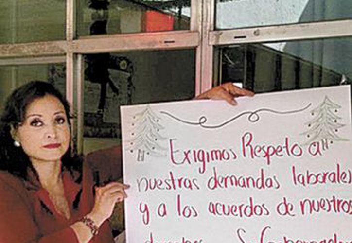 Una de las maestras inconformes, con una cartulina de protesta, en una de las más de mil escuelas que cerraron por el paro. (Milenio)