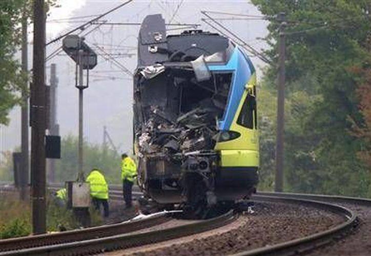 Empleados trabajan cerca de un tren dañado luego de impactar con un camión cerca de Ibbenbueren, al oeste de Alemania. (Agencias)