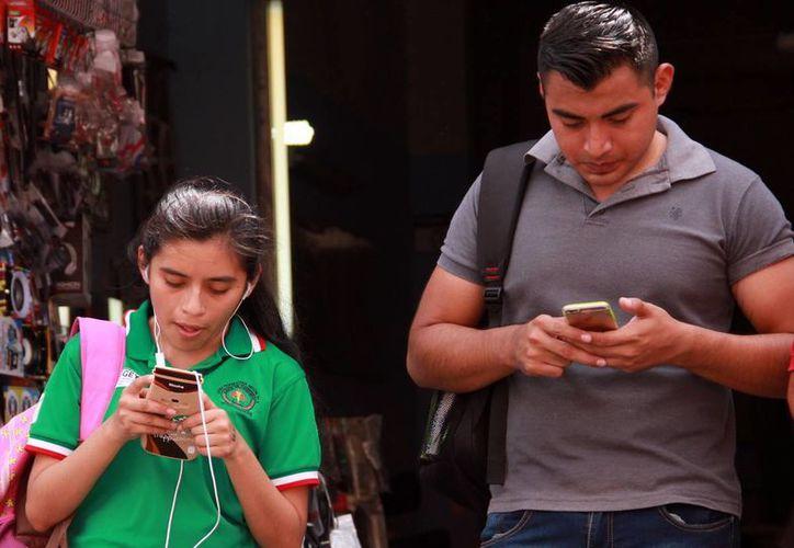 Los doctores recomiendan evitar un uso excesivo de la tecnología. Imagen de dos jóvenes que revisan su celular en una calle de Mérida. (Milenio Novedades)