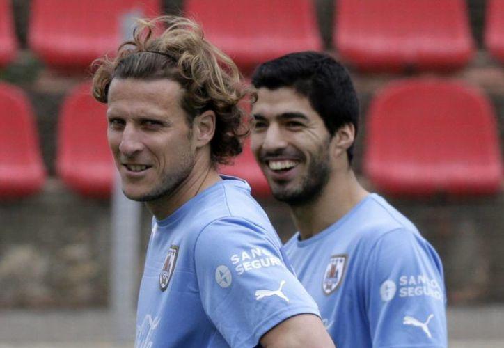 Forlán (i) sí será titular en el partido entre Uruguay y Costa Rica, pero Luis Suárez no. (EFE)
