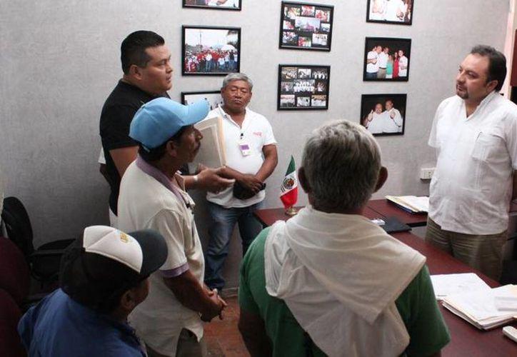 El diputado Francisco Torres Rivas habla con trabajadores de la desaparecida Sidra Pino. (SIPSE)