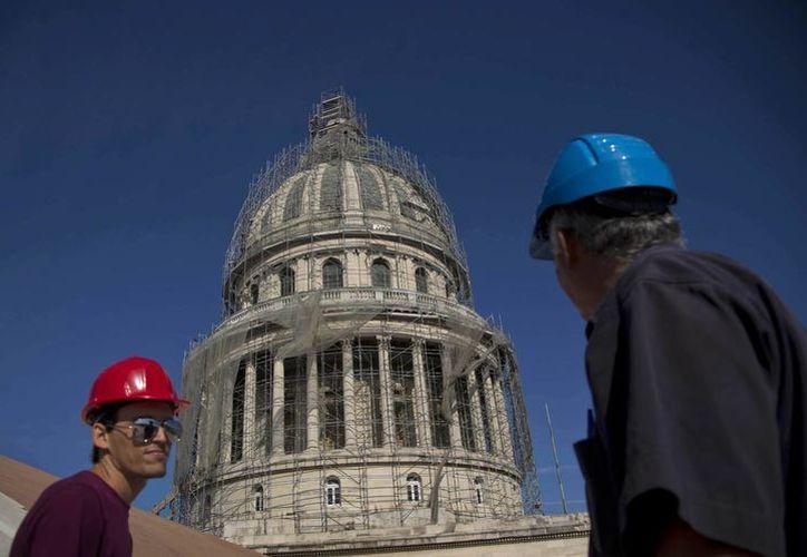 Dos trabajadores restauran el Capitolio de la Habana, Cuba, inaugurado en 1929 y que es similar al de Estados Unidos. (Archivo/AP)