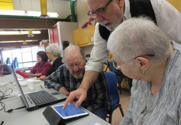 El Curso de Verano para Adultos Mayores del DIF Municipal se realizará del 20 al 24 de julio. Imagen de un grupo de ancianos que aprenden el uso de dispositivos móviles. (Archivo/Notimex)