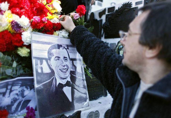 Un hombre deja flores en la tumba de Carlos Gardel, en el Cementerio de la Chacarita en Buenos Aires, Argentina, al cumplirse un año más de su muerte. (EFE/Archivo)
