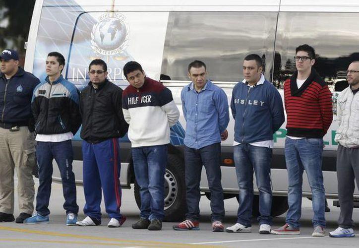 La policía custodia a los siete colombianos acusados de asesinar a un agente de la agencia antidrogas estadounidense DEA antes de extraditarlos a Estados Unidos. (Agencias)