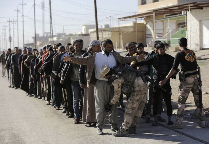 Mosul, capturada por el grupo Estado Islámico en 2014. Soldados iraquíes registran a grupo de hombres en el vecindario de Gogjali, en Mosul. (AP/Hussein Malla)