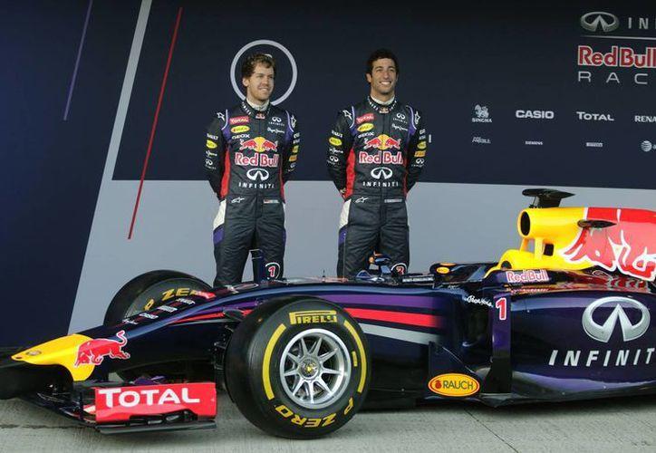 Vettel (i) y su compañero de equipo, el australiano Daniel Ricciardo, durante la exhibicón del nuevo auto de la escudería Red Bull. (Agencias)