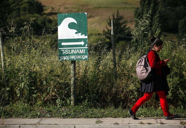 Una niña camina junto a un cartel que señala la ruta de evacuación en caso de que llegase un tsunami a Navidad. (Agencias)