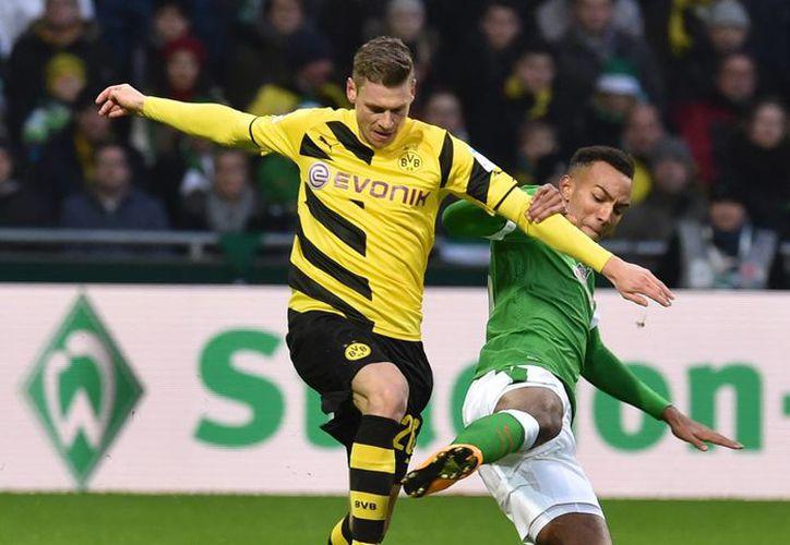 Lukasz Piszczek (i), del Dortmund, se enfrenta deportivamente a Melvyn Lorenzen, cuyo equipo Werder Bremen ganó y hundió más al equipo de Borussia. (Foto: AP)