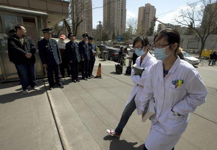 Trabajadores de salud de China, con máscaras, pasan junto a un grupo de guardias de seguridad que bloquean el Ministerio de Salud de China. (Agencias)