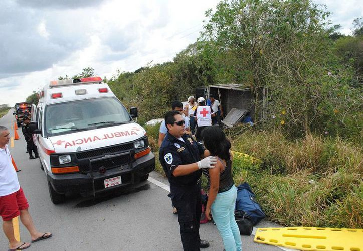 Imagen de la fuerte volcadura ocurrida ayer en el tramo Tizimín-Río Lagartos. Un paramédico revisa a una de las lesionadas del accidente. (Milenio Novedades)