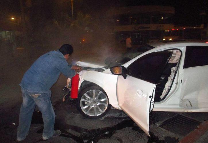 El empleado de una gasera controló, con un extintor, el fuego dentro del Mazda . (Redacción/SIPSE)