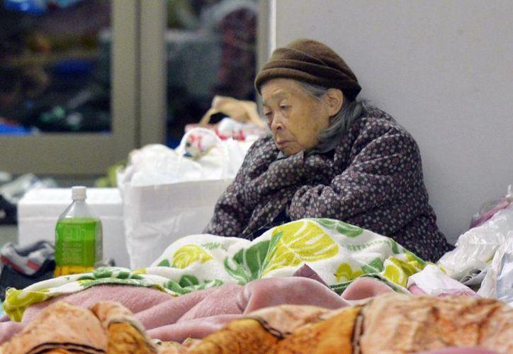 Una mujer se apoya en un refugio en Mashiki, prefectura de Kumamoto, Japón. (Agencias)