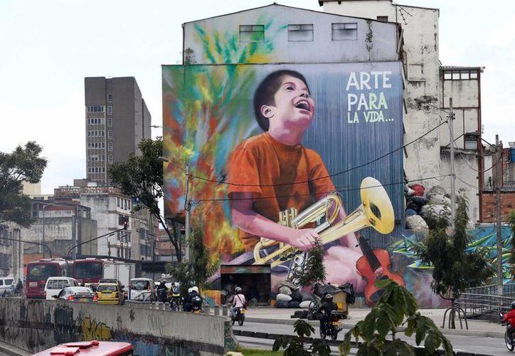 Un niño sostiene una trompeta en este grafiti de Bogotá fotografiado el 13 de marzo del 2015. (Agencias)