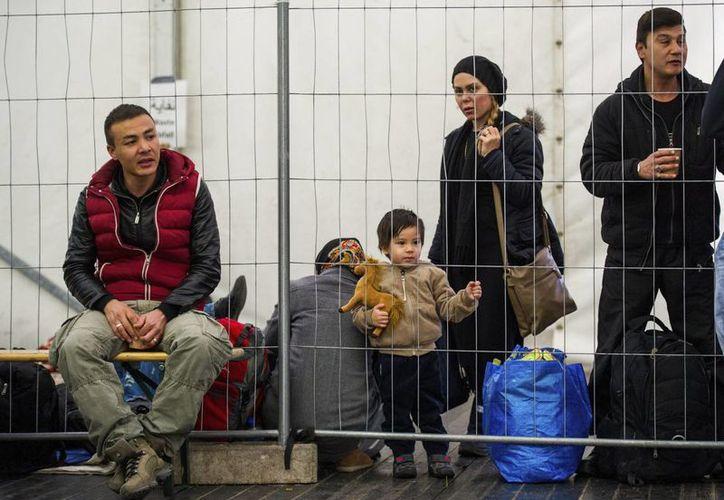 Varios refugiados esperan para registrarse en un campamento temporal. (Archivo/EFE)