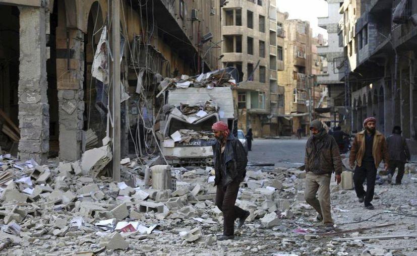 El bombardeo es el primero de este año realizado por el ejército del aire de Francia contra el Estado Islámico en Siria. Varias personas caminan entre los escombros de un edificio en una calle de Douma, afueras de Damasco. (Archivo/EFE)