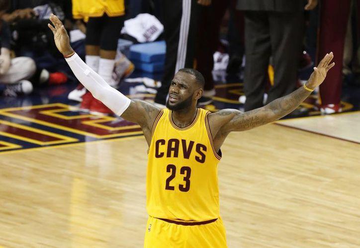 Le Bron James, de Cavaliers, arenga a la multitud en la segunda mitad del tercer partido de la serie final de la NBA ante Warriors de Golden State. (AP)
