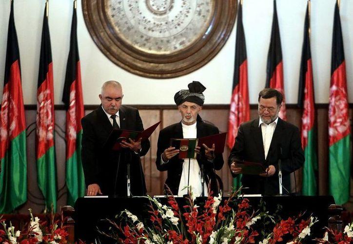 Ashraf Ghani Ahmadzai (c) toma juramento a dos vicepresidentes durante su ceremonia de inauguración en el palacio presidencial en Kabul, Afganistán. (Agencias)