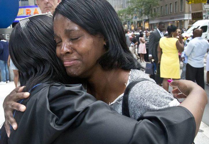 Candie Hailey (der), llora mientras abraza a su hermana Chyna tras su graduación universitaria en Nueva York. Candie pasó dos años y un tercio en aislamiento en el penal de Rikers. (Agencias)