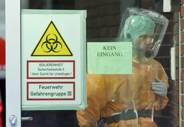 Un trabajador hospitalario con traje protector entra en una habitación de aislamiento. (Archivo/EFE)