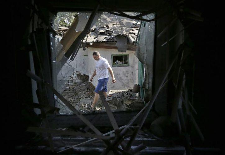 Un residente inspecciona los daños cerca de las casas destruidas después de los bombardeos en Donetsk, Ucrania. (Agencias)