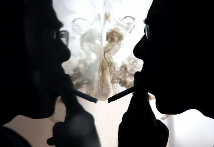 El comercio ilícito de cigarros es una grave amenaza para la salud pública. En la imagen una persona fuma un cigarro mientras se observa frente a un espejo. (Archivo/EFE)