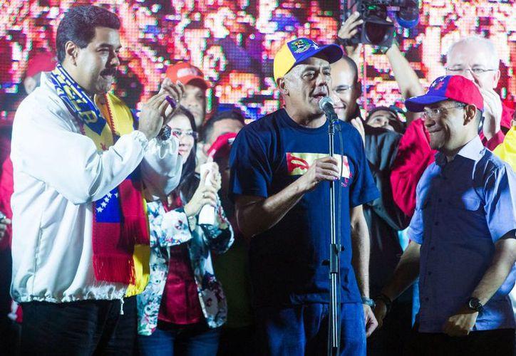 El alcalde reelecto de Libertador de Caracas, el oficialista Jorge Rodríguez (c), festeja con el presidente Nicolás Maduro (i), las victorias obtenidas en los comicios. (EFE)