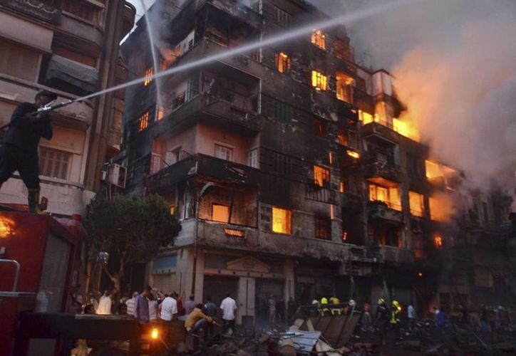 Personas observan a bomberos combatiendo el fuego originado en un hotel de seis pisos en el populoso barrio de Ataba, en El Cairo, Egipto, el 9 de mayo de 2016. (EFE)