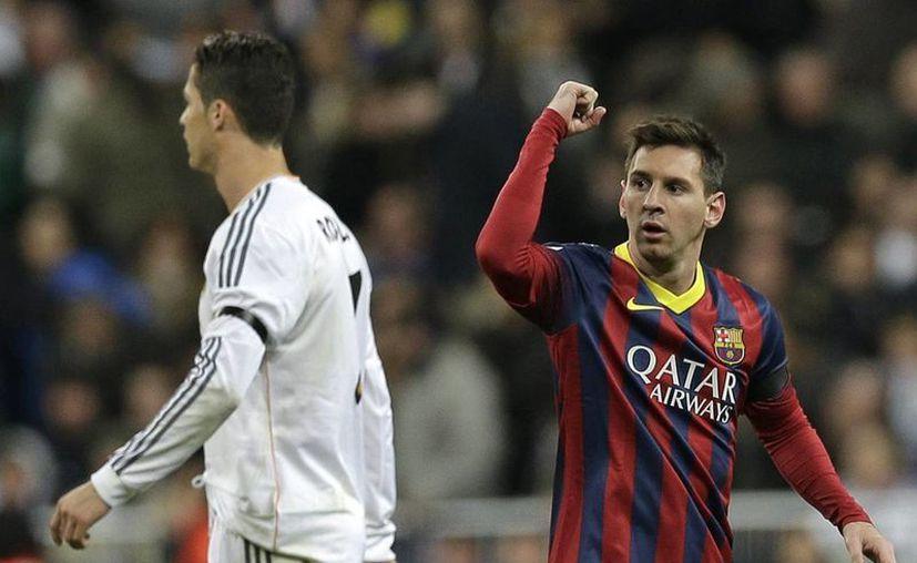 Lionel Messi (d) ofreció una actuación descomunal que incluyó tres goles decisivos para dar al Barcelona una victoria 4-3 en cancha del Real Madrid. (Agencias)
