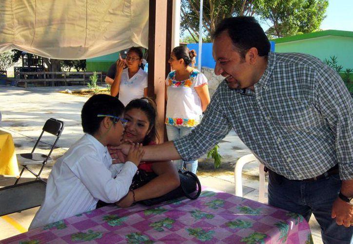 El diputado Francisco Torres Rivas saluda a un niño en el fraccionamiento Loma Bonita. (Milenio Novedades)