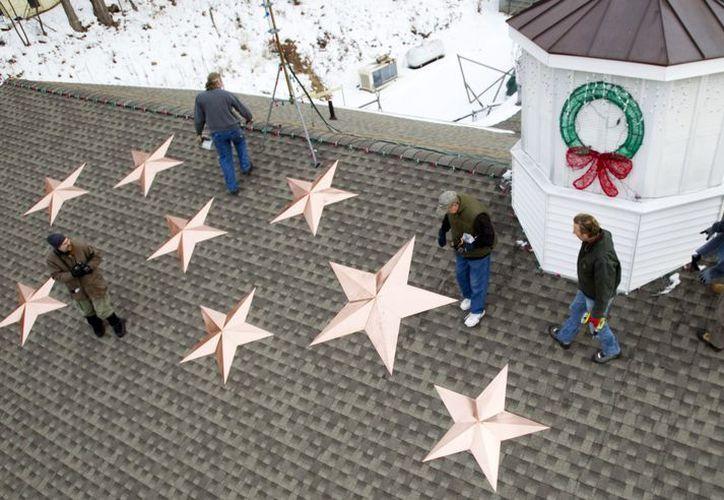 Personas instalan 26 estrellas en el techo de la estación de bomberos de Sandy Hook en honor de cada una de las víctimas del tiroteo del 14 de diciembre. (Agencias)