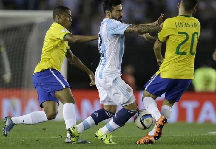 Ezequiel Lavezzi (c) disputa la pelota contra Lucas Lima. El primero anotó por Argentina y el segundo por Brasil, que sacó el empate como visitante en partido de la eliminatoria de Conmebol rumbo al Mundial de Rusia 2018. (AP)