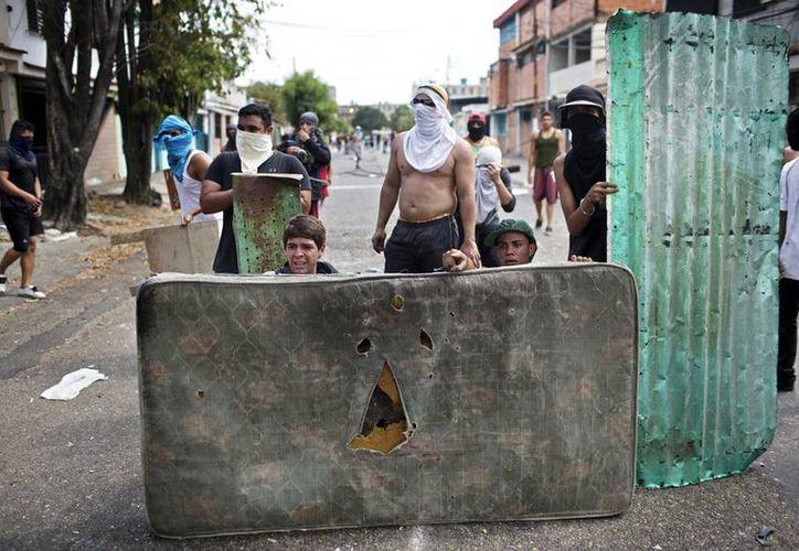 Los manifestantes usan un colchón para protegerse durante los enfrentamientos con la policía durante una protesta contra el Gobierno en Venezuela. (Agencias)