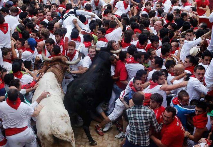 Dos toros embisten a una multitud de corredores en el encierro de este sábado en Pamplona. (AP)