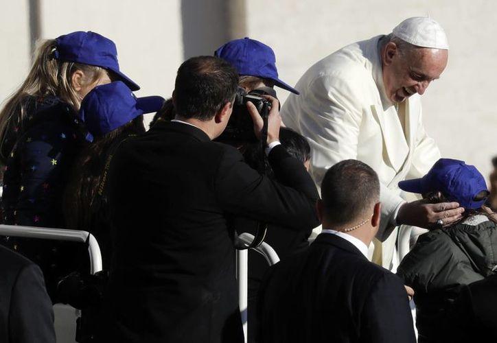 El Papa Francisco da la bienvenida a algunos niños en su papamóvil mientras llega a la Plaza de San Pedro para asistir a su audiencia general semanal, en el Vaticano. (AP/Gregorio Borgia)