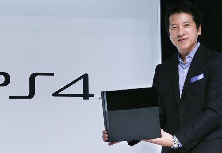 Hiroshi Kawano, jefe del sector de videojuegos de Sony Corp. para Japón y Asia, sostiene una consola PlayStation 4 durante un acto en Tokio. (Agencias)