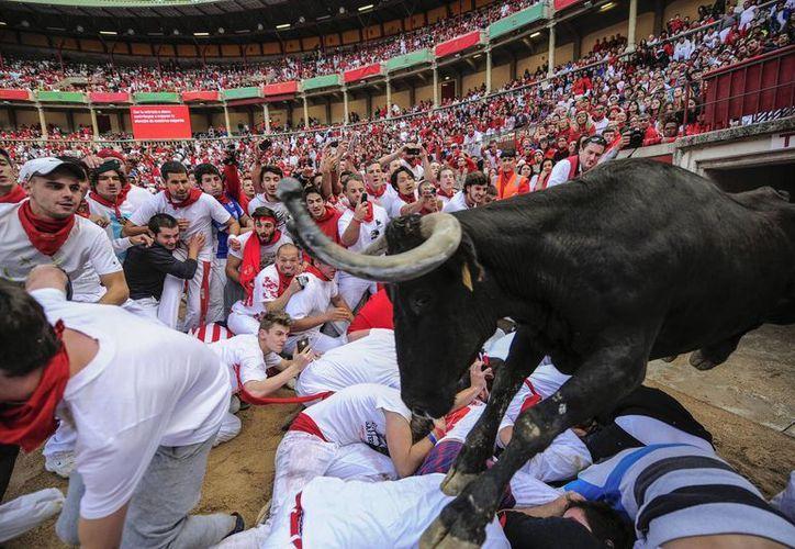 Un toro de lidia salta sobre varios corredores al llegar a la plaza de toros, punto final de la segunda corrida de los Sanfermines, este martes en Pamplona, España. (Foto: AP)