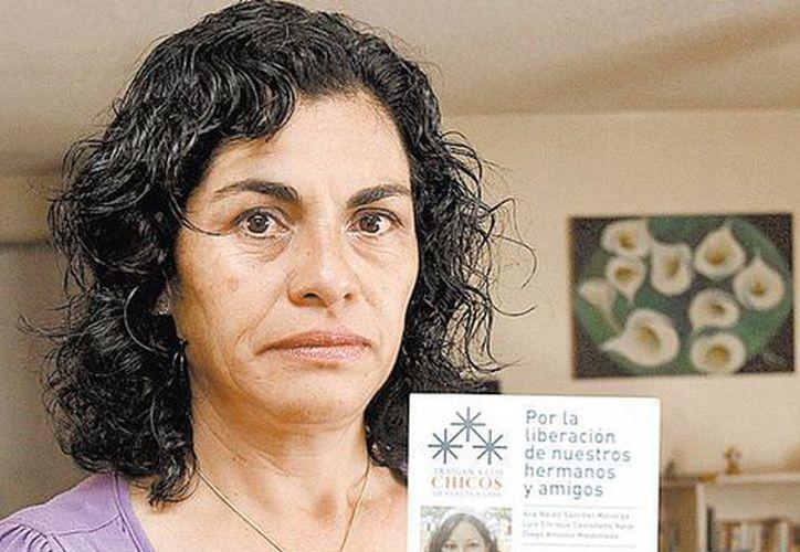 Guadalupe Nava muestra imágenes de las tres víctimas. (Milenio)
