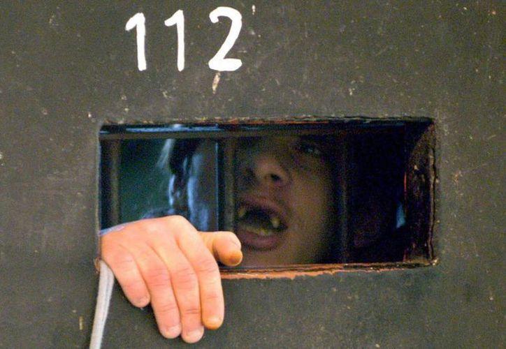 Un recluso uruguayo reclama mejores condiciones de vida, desde la ventanilla de su celda. (Archivo/EFE)
