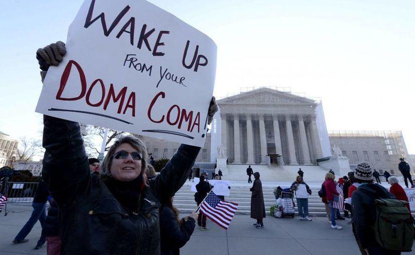 """Una partidaria de los matrimonios de personas del mismo sexo sostiene un cartel en el que se lee """"¡Despierta DOMA del coma!"""". (EFE)"""