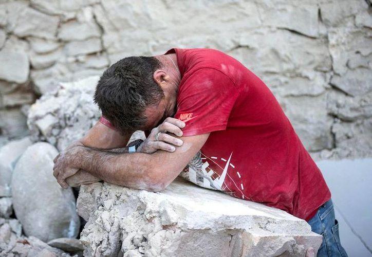 Una hombre llora sobre los restos de un edificio en Amatrice, Italia, una de las ciudades devastadas por el sismo de magnitud 6 que azotó, la madrugada de este miércoles, gran parte del territorio de Italia. (AP)