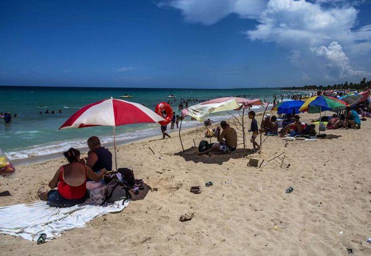 Bañistas sentados en primera línea de playa en medio de latas vacías y basura cerca de La Habana, en Cuba. (AP/Desmond Boylan)