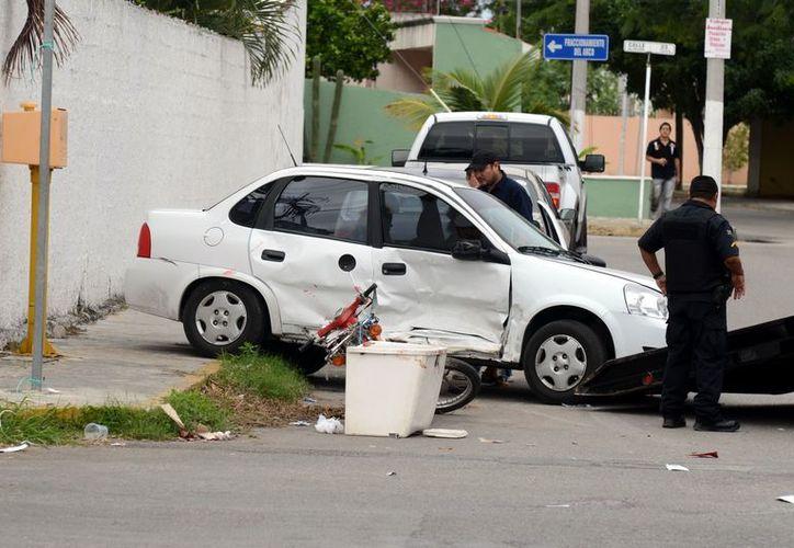 El Chevy recibió varios impactos, ante el horror de su conductora, que no podía creer lo que ocurría. (Cuauhtémoc Moreno/SIPSE)
