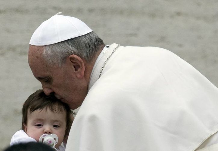 El Papa Francisco besa a un niño al llegar a la Plaza de San Pedro para su audiencia semanal. (Agencias)